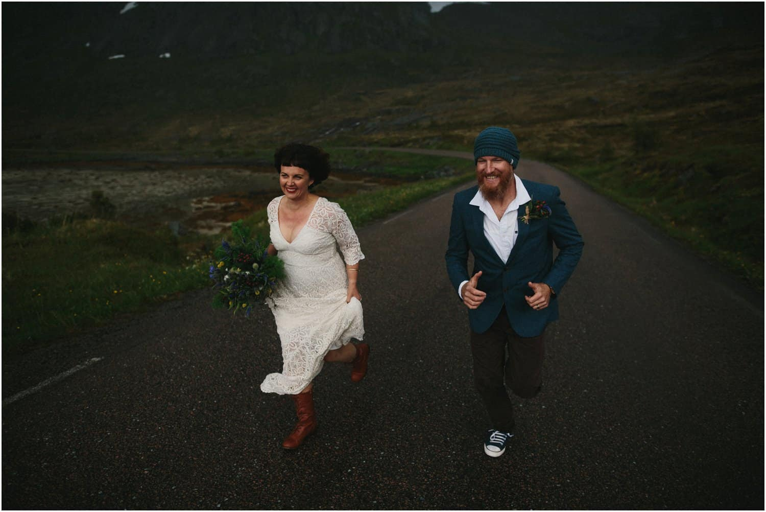 A newly married couple run from the rain during their Lofoten Islands elopement