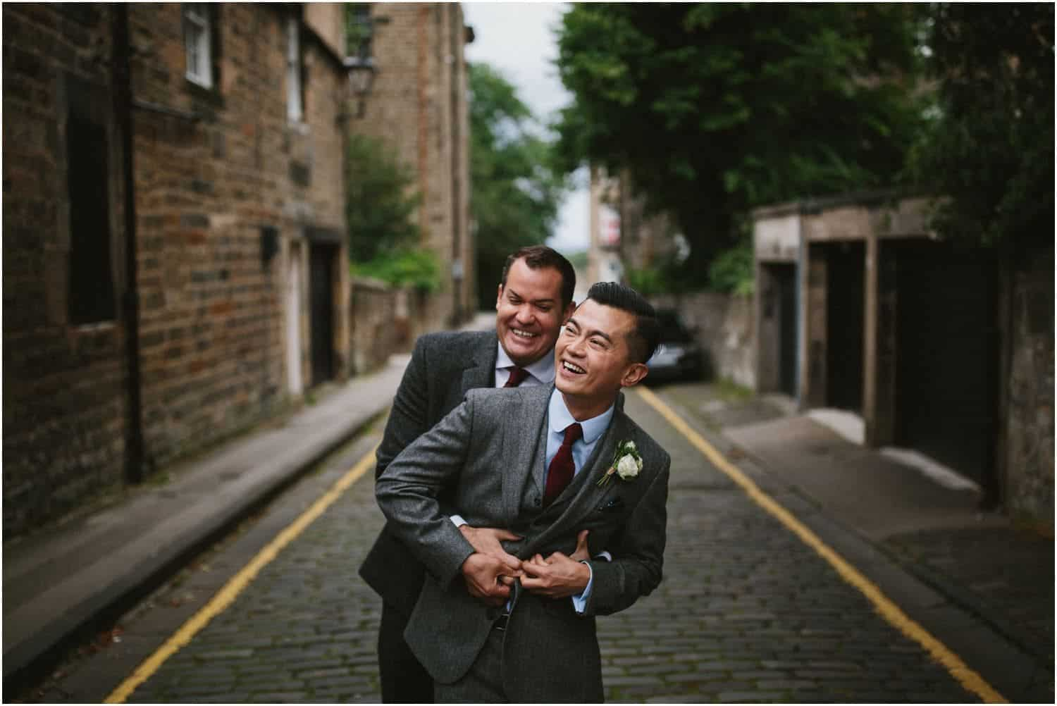 A same sex couple embrace in the streets at their Timberyard Edinburgh wedding