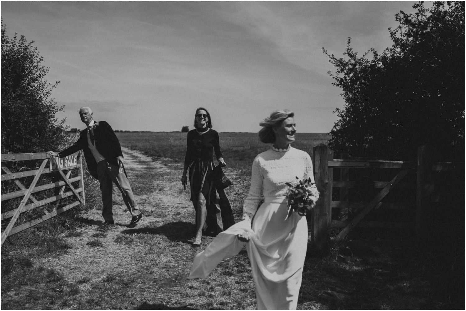 A bride and her parents walk through a field towards the Church at this Isle of Wight wedding