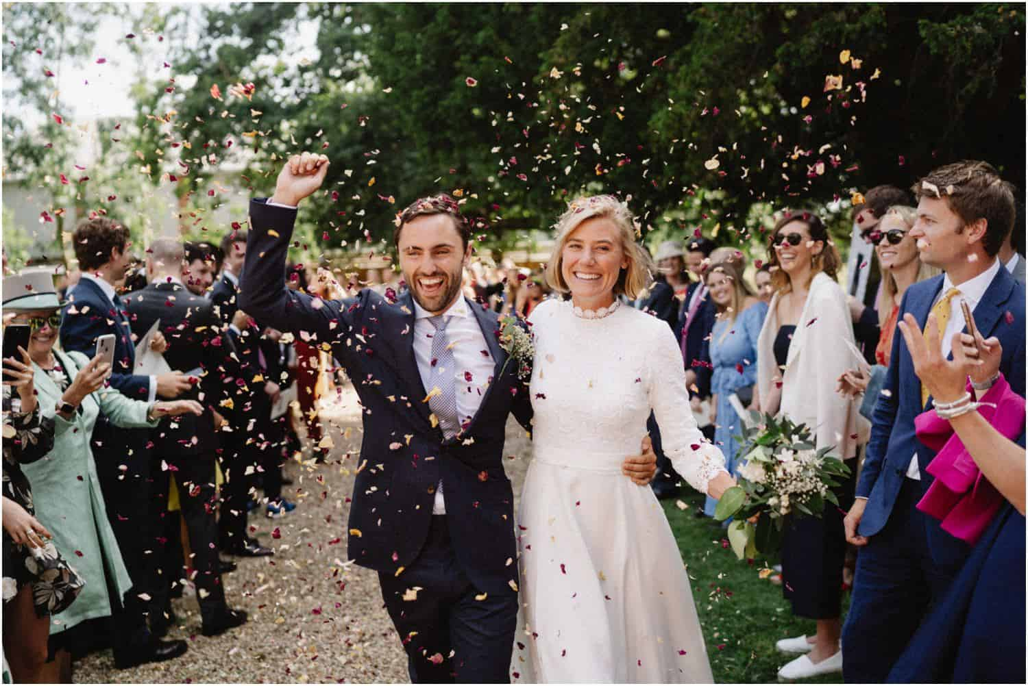 A newly married couple are covered in confetti thrown by their friends at their Isle of Wight wedding