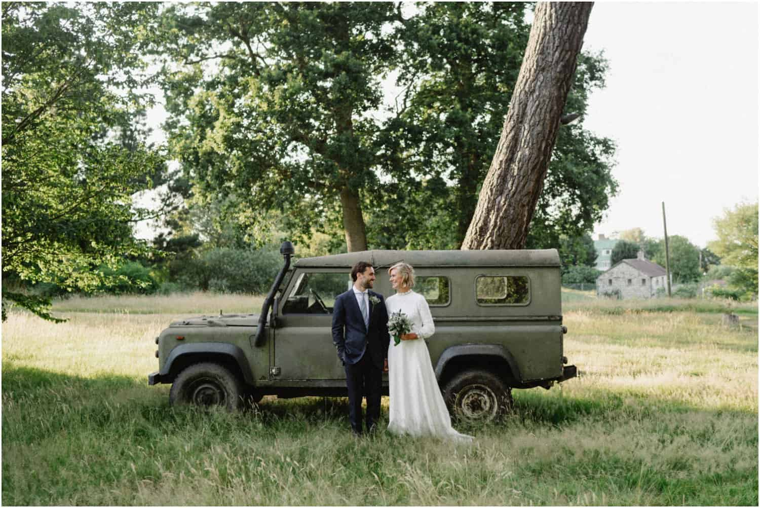 A bride and groom stand in front of an old Land Rover at their Isle of Wight wedding