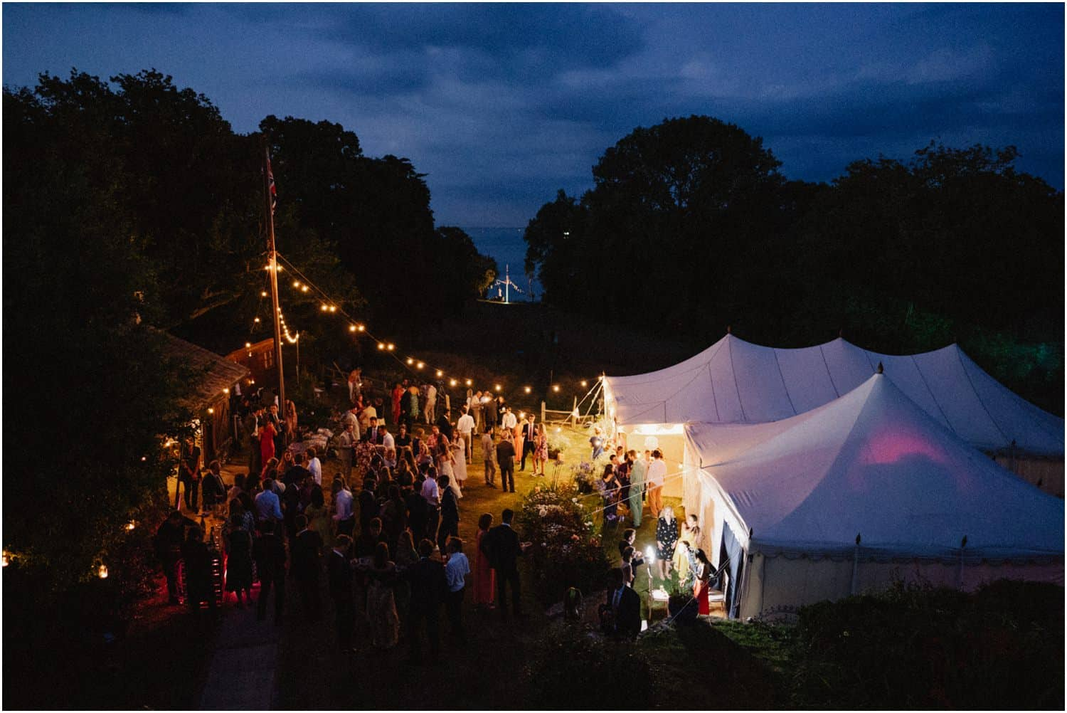 A night time view of a beautiful Isle of Wight wedding, with a marquee and lanterns in the foreground, and the ocean in the background