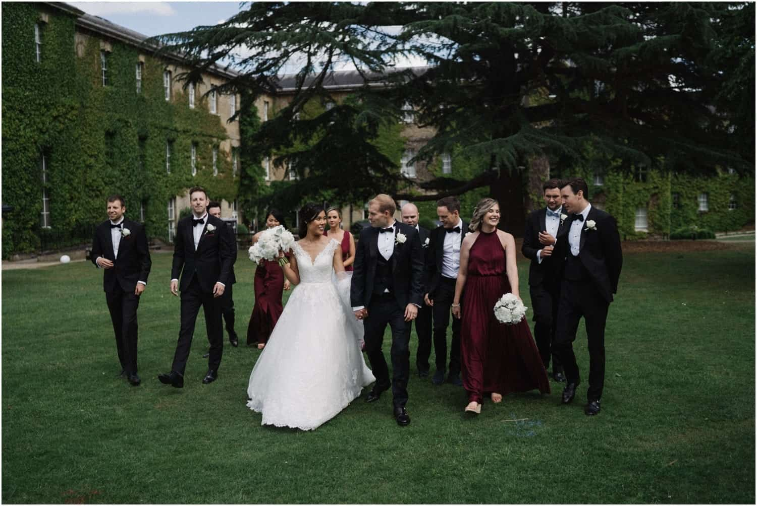 A bridal party walk through beautiful grounds at a De Vere Beaumont Estate wedding in Windsor