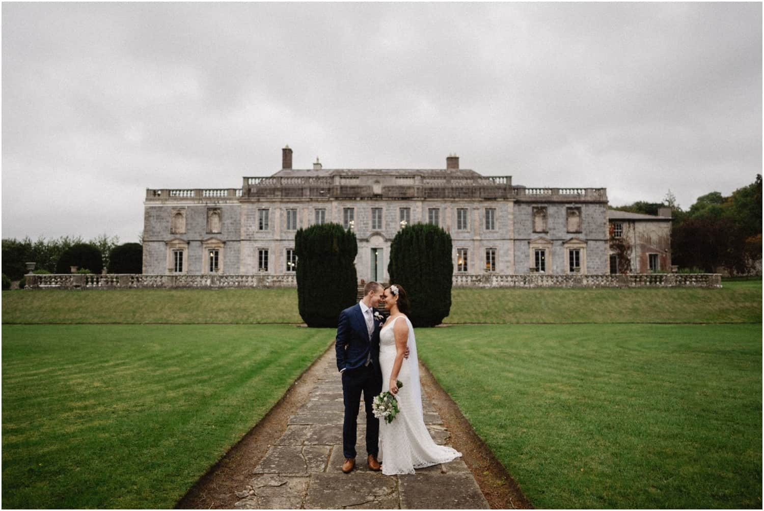 A newly married couple stand in front of the main building at their Gloster House wedding