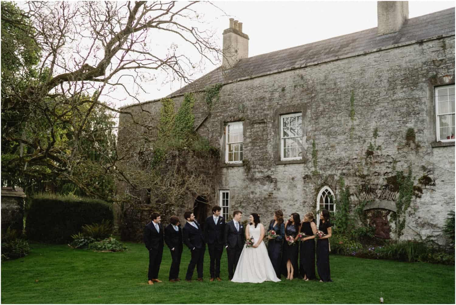 A bridal party stand near an old building at a Durhamstown Castle wedding